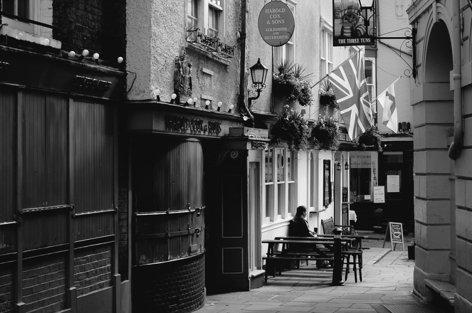 A man sits alone outside a pub in Windsor to have a drink.